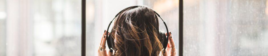 Frau steht am Fenster und hört Podcasts auf podcast.de